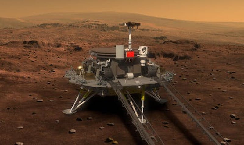 A boxy spacecraft standing on legs on barren red dirt with tracks for a rover to roll down.