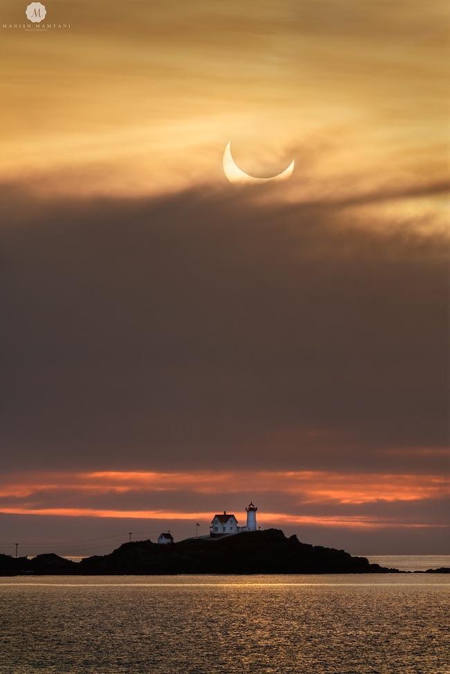 An island with a lighthouse with a hazy, cloudy morning sky and an eclipsed sun peeking through aboe.