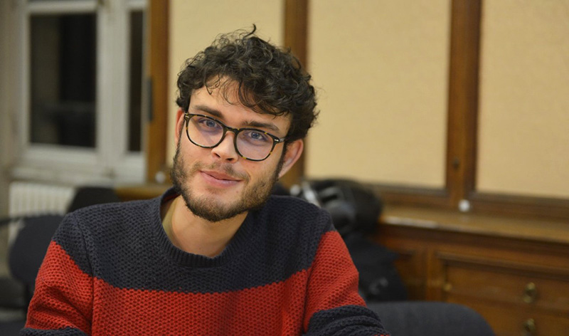 Young smiling man with glasses, short beard and messy hair.