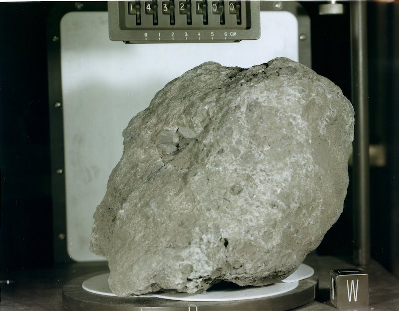 A grey rock that's somewhat oval with a rough flatter texture on one side.