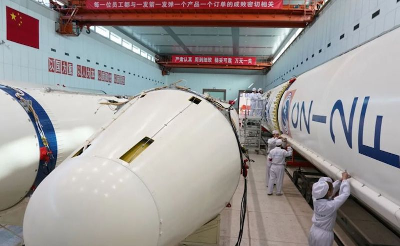 Staff in white uniforms are working in a room with giant, white rocket parts.