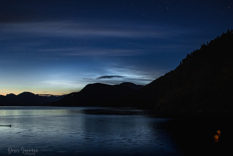 Light clouds streak across a dark blue scene with a river below and mountain silhouettes that divide the water from the sky.