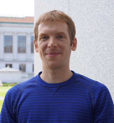 Smiling young man with short red hair, wearing a blue shirt, and a building behind him.