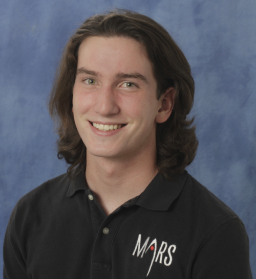 Young man with dark, shoulder-length hair in Mars polo shirt.