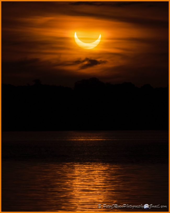 Crescent solar eclipse glowing through clouds over water.