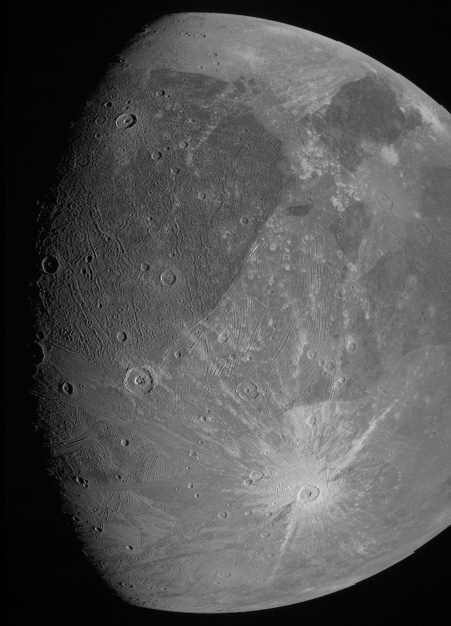 Moon-like body with craters, light and dark spots and streaks.