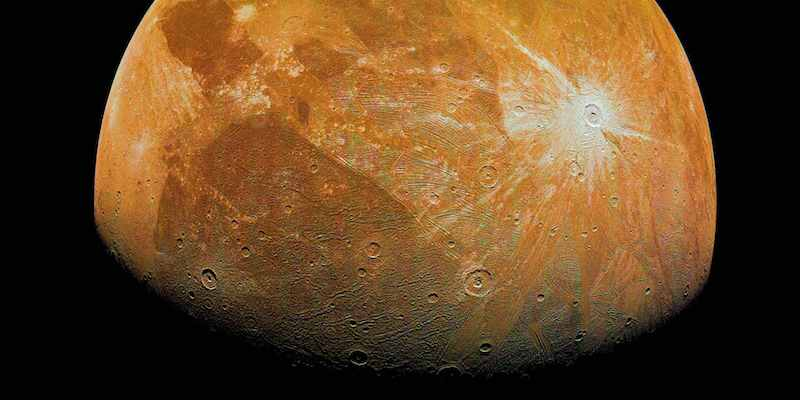 Orange moon-like body with craters and light and dark spots.