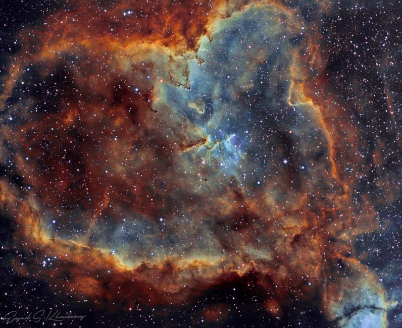 Red, blue and brown very detailed clouds of gas and dust in starry space.