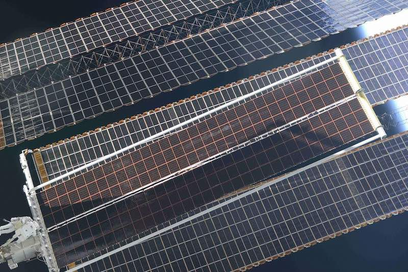 Solar array upgrade. Panels look like massive plates with a checkerboard print. Small space-suited figures.