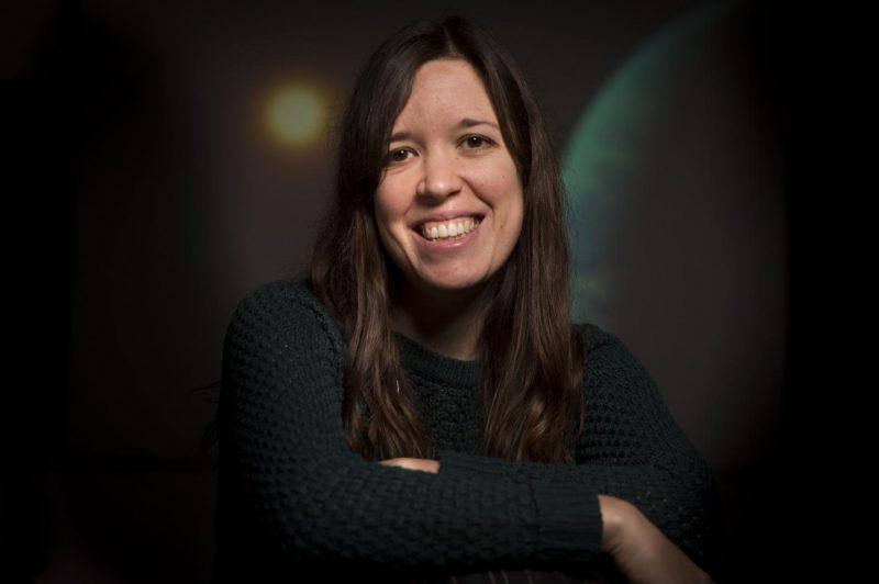 Una mujer de largo cabello negro sonriendo con los brazos cruzados.