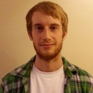 Hombre joven con barba, camisa a cuadros y camisa blanca.
