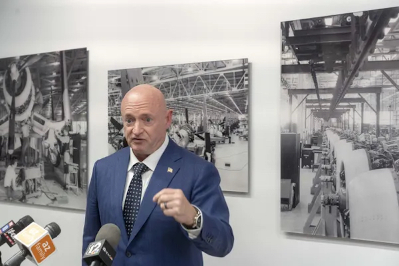 Man in blue suit standing in front of posters of rocket construction.