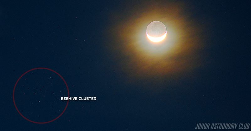 Crescent moon with earthshine near star cluster.