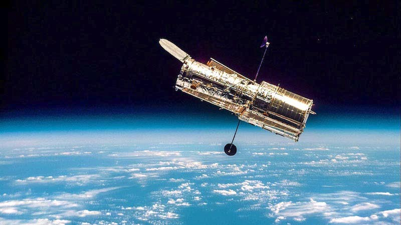 A metallic canister, the Hubble telescope, floats above our blue Earth.
