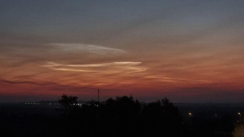 Dark horizon, orange to blue sky with whitish wispy clouds.