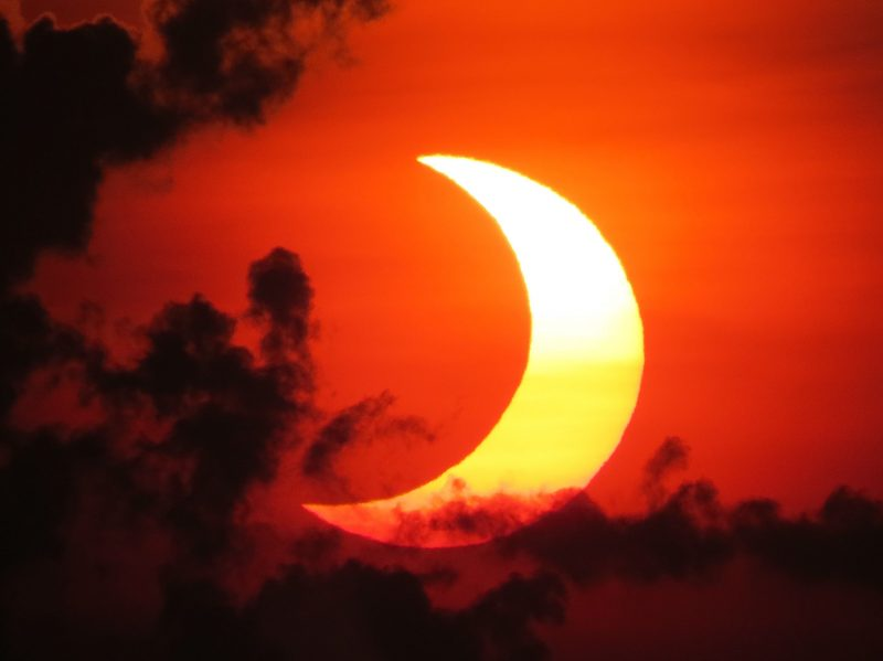Orange sky patchy black clouds and lighter crescent of sun from behind moon.