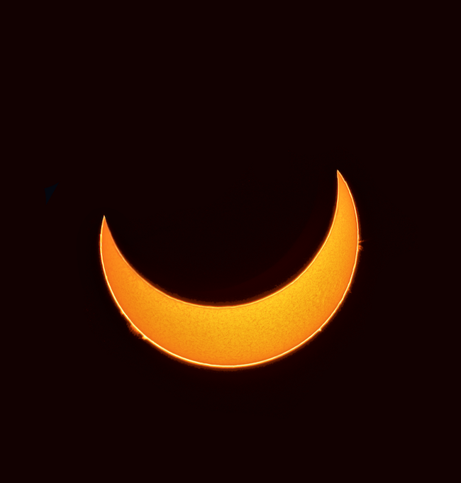 Crescent sun during eclipse, with prominences along the edge as viewed through an H-alpha filter.
