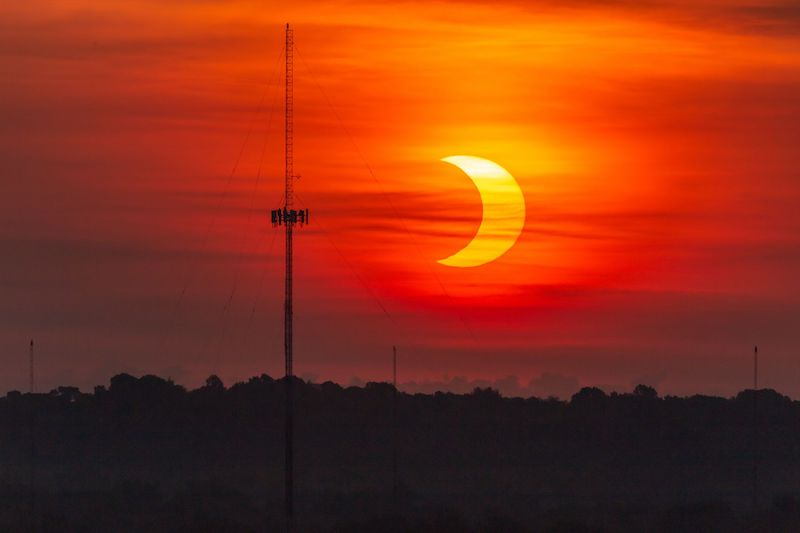 Red hazy sky with a crescent eclipsed sun and a high radio antenna in the foreground.