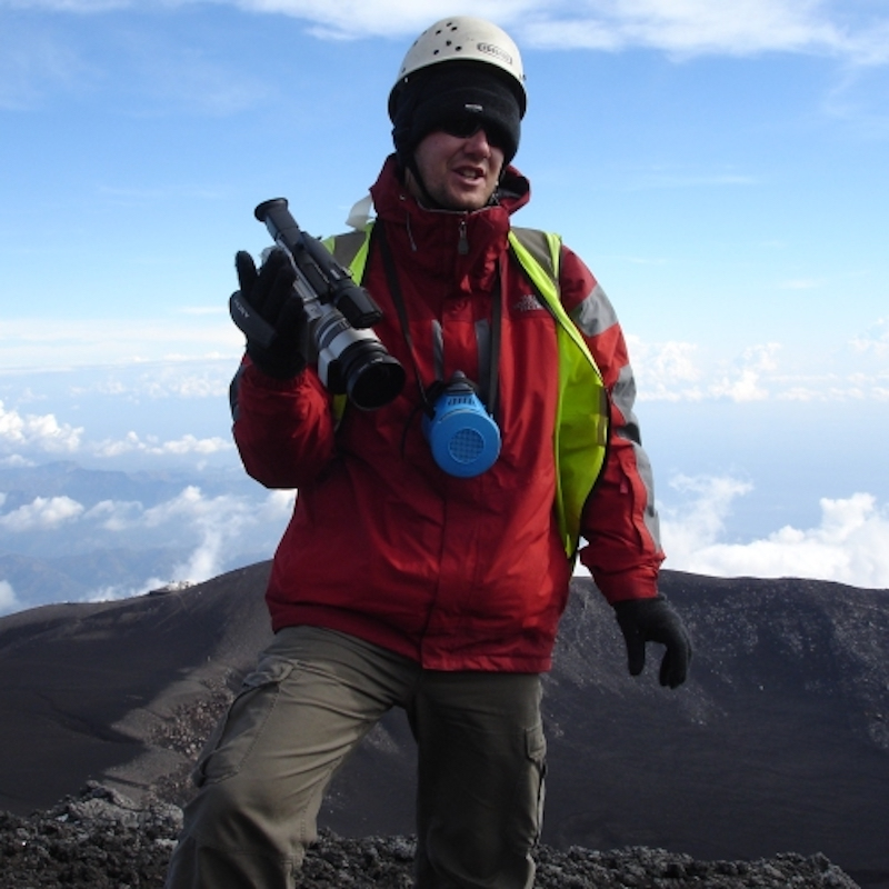 Man in hiking gear with clouds and barren mountain behind him.