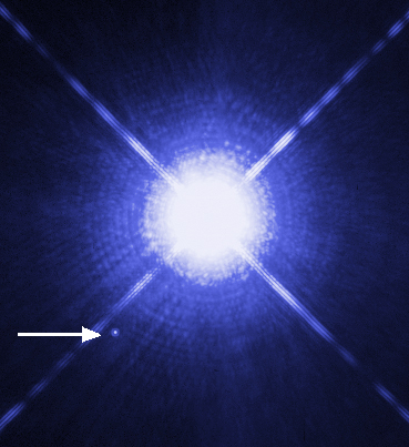 A very bright star, next to a tiny faint star, pointed out by an arrow.