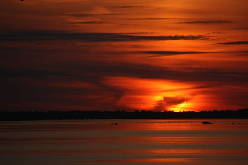 Eclipse rising over lake with many streaked orange and red clouds.