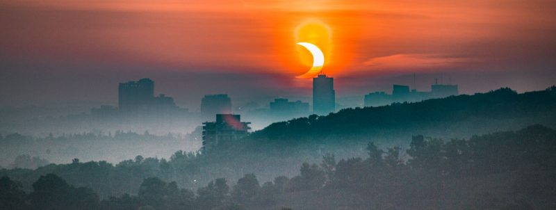 Foggy cityscape in foreground of crescent eclipsed sun.