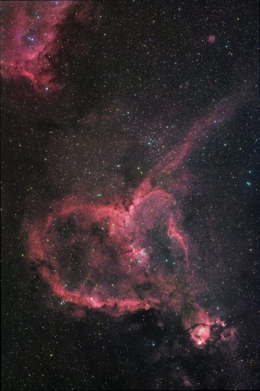 Pink-red heart-shaped cloudy form in space against star field.
