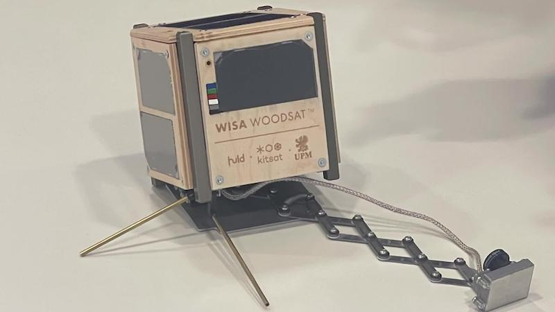 A wooden box with writing on its face, plus metal features like legs and a camera jutting out from its body.