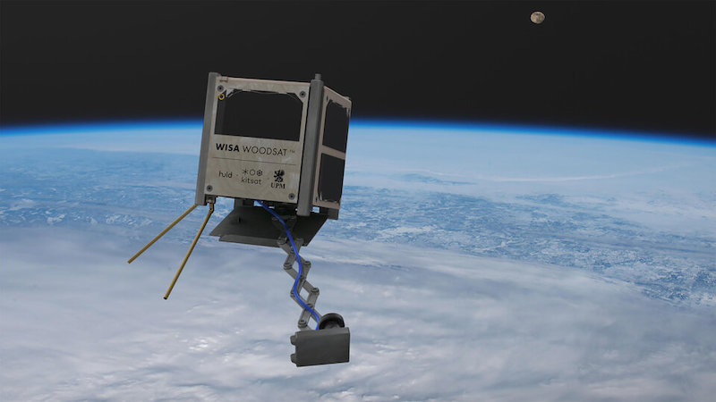A cubical wooden satellite floating in space above Earth with a metal boom jutting outward.