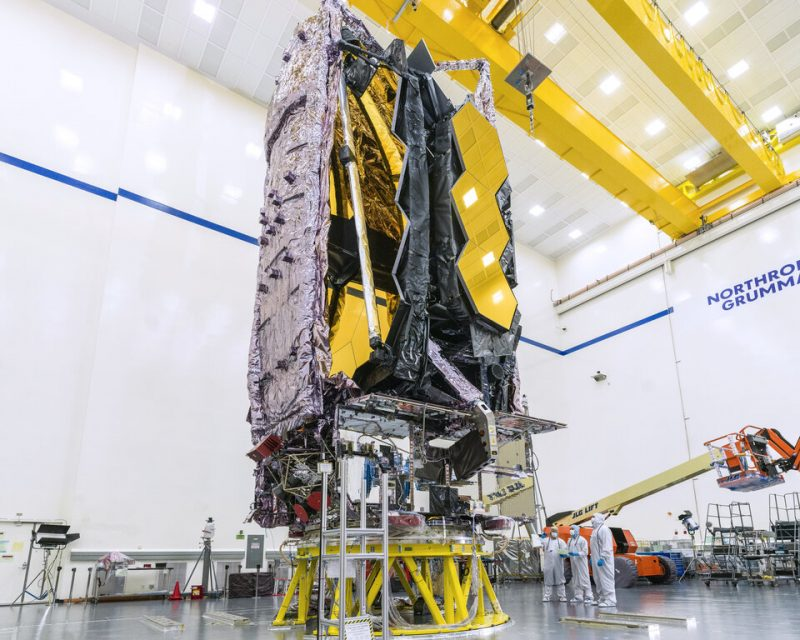 Webb Telescope: A huge boxy structure poised on scaffolding in a giant white clean room.
