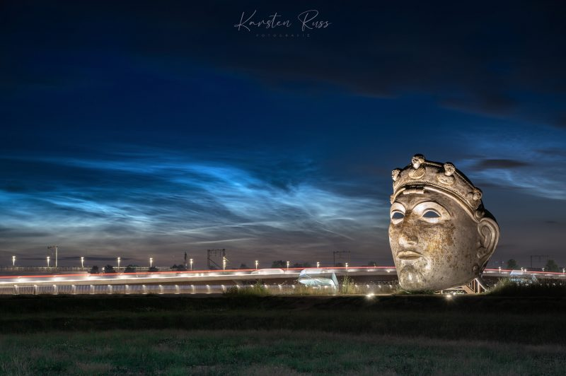 Night-shining clouds over a cityscape, with a statue of a huge stone head in the foreground.
