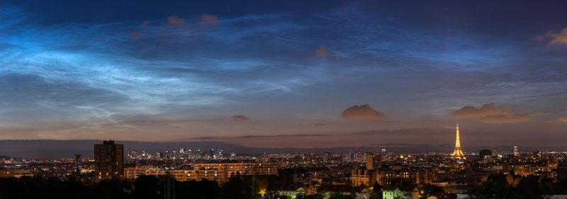 A panorama showing bright clouds at night, above the Eiffel Tower.