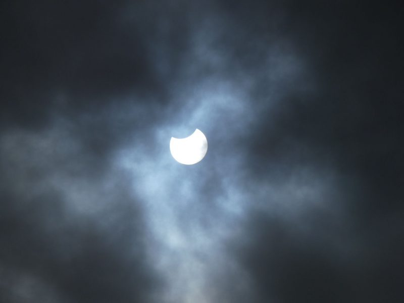 Clouds with white sun peering out with small dark piece missing.