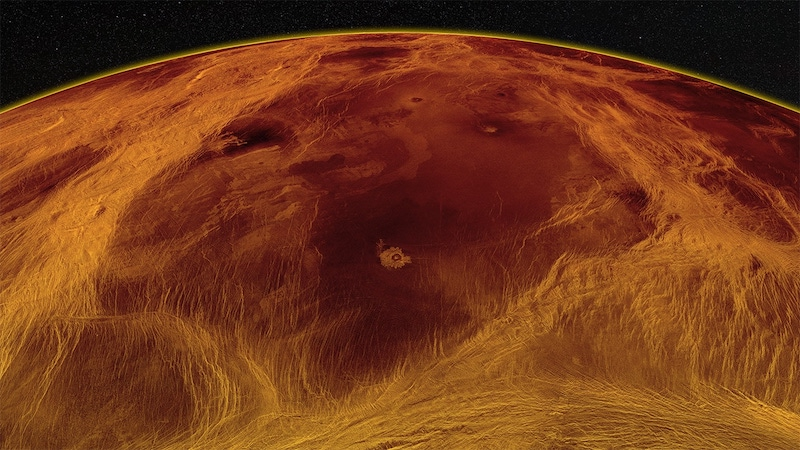 Cracked surface of Venus from space, with dark block surrounded by wispy streaks, looking like pack ice tectonics.