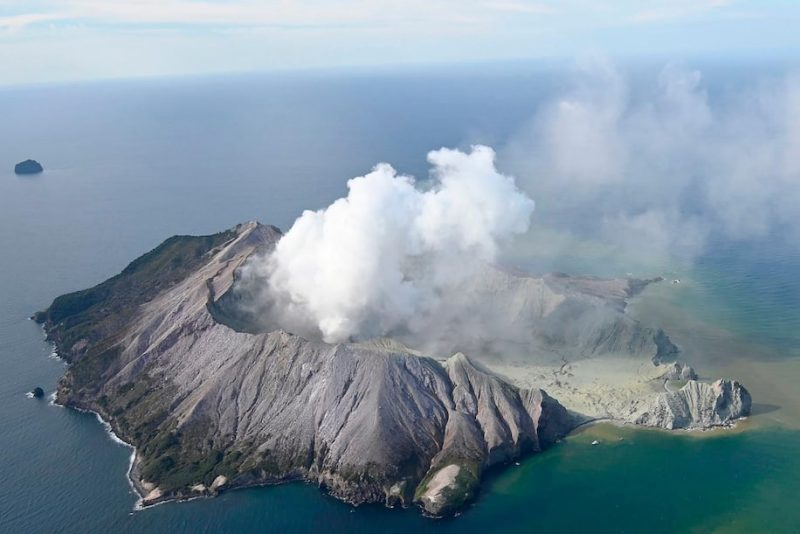 Volcano surrounded by ocean, with smoke pouring from its caldera.