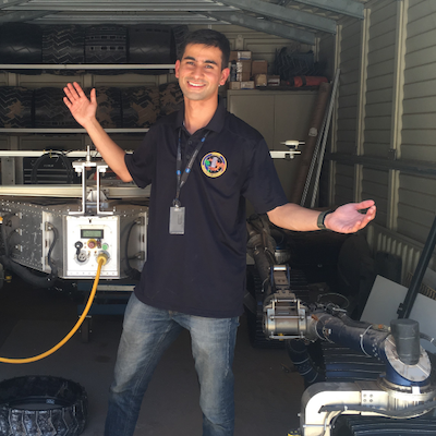 Smiling man standing in front of electrical equipment.