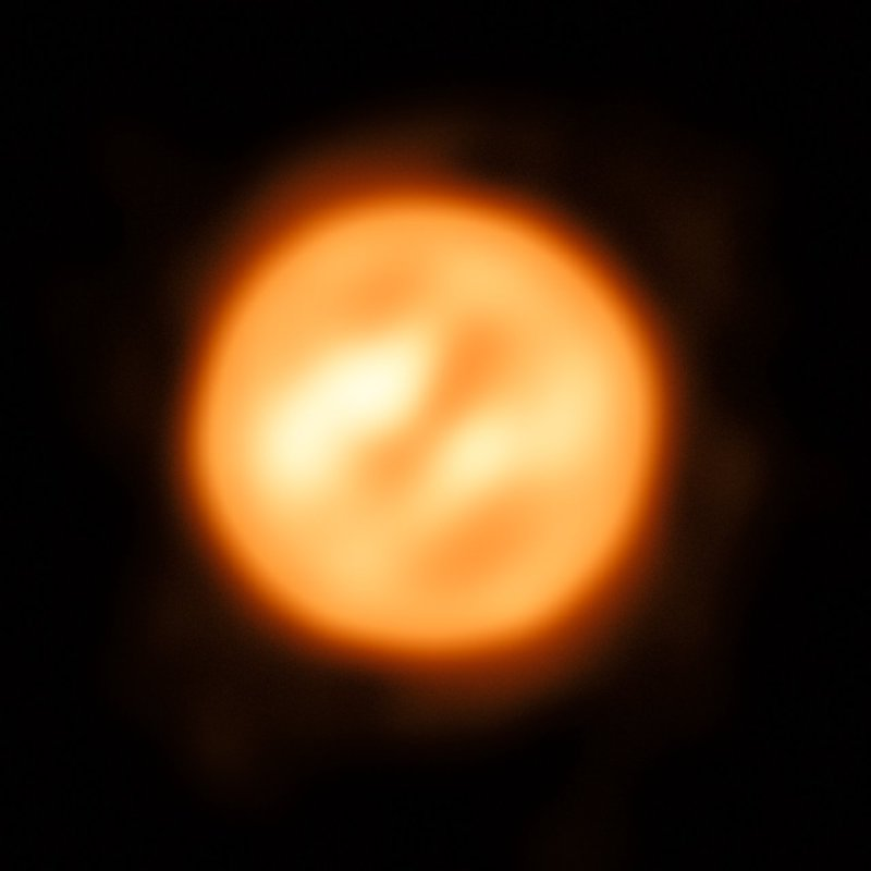 An orange disk with two prominent elongated yellowish features on it.