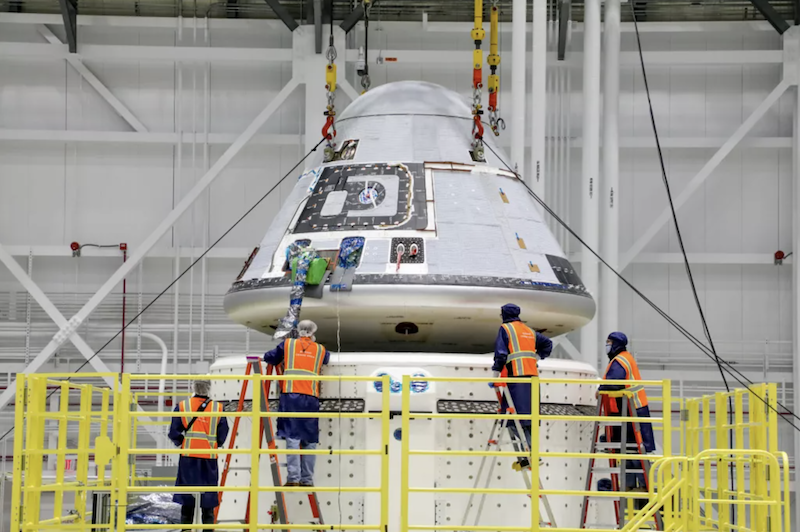 A white cone shaped fixture, the starliner, is examined by people wearing orange vests in the middle of a white room.