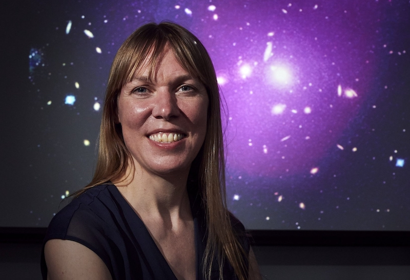 A woman with long blonde hair smiles in front of a mural of stars and galaxies.