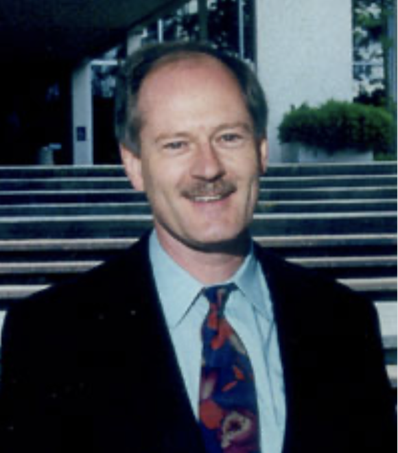Smiling man with mustache in a suit jacket, in front of steps.
