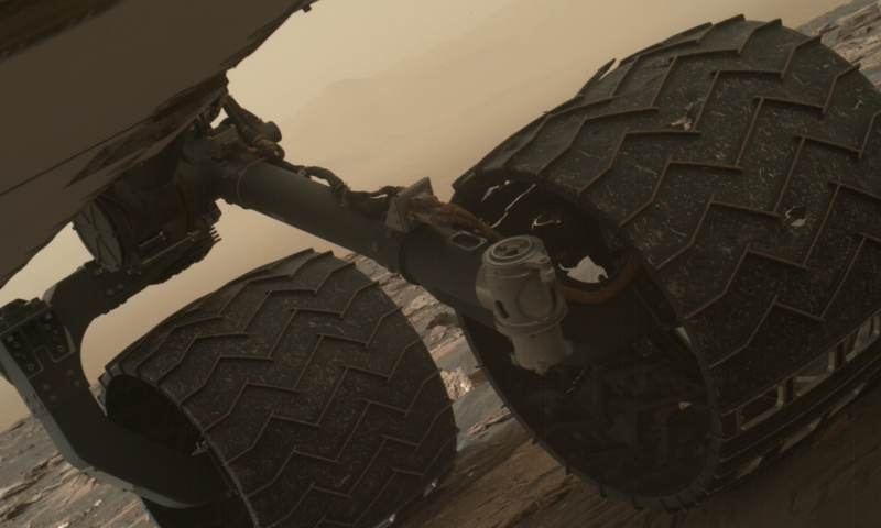 Large rover wheels in front of a red desert background.