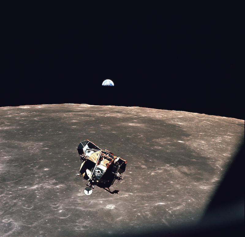 A moon lander above a brown/beige moon, with a crescent Earth behind.