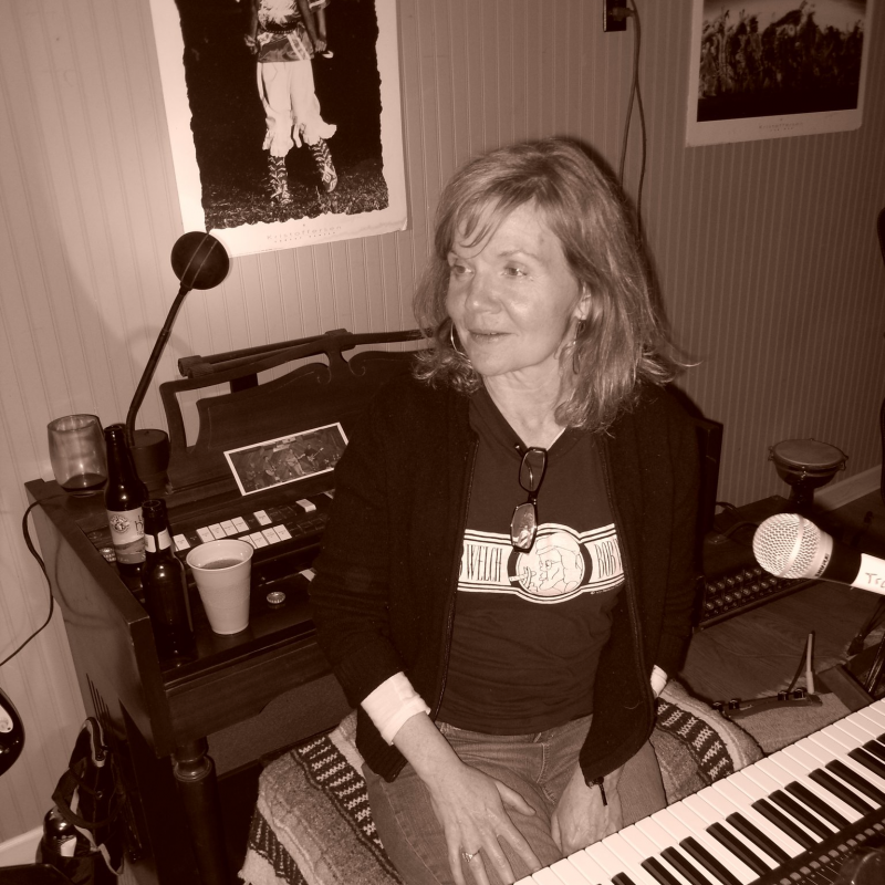 Sepia-toned photo of a woman seated at a keyboard.