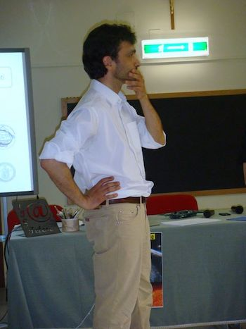 Standing man with one hand on his chin and one on his hip, with table and blackboard behind him.