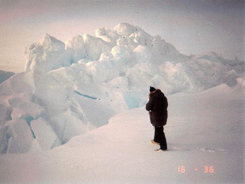 Man in dark Arctic garb standing in snow in front of piled ice chunks.