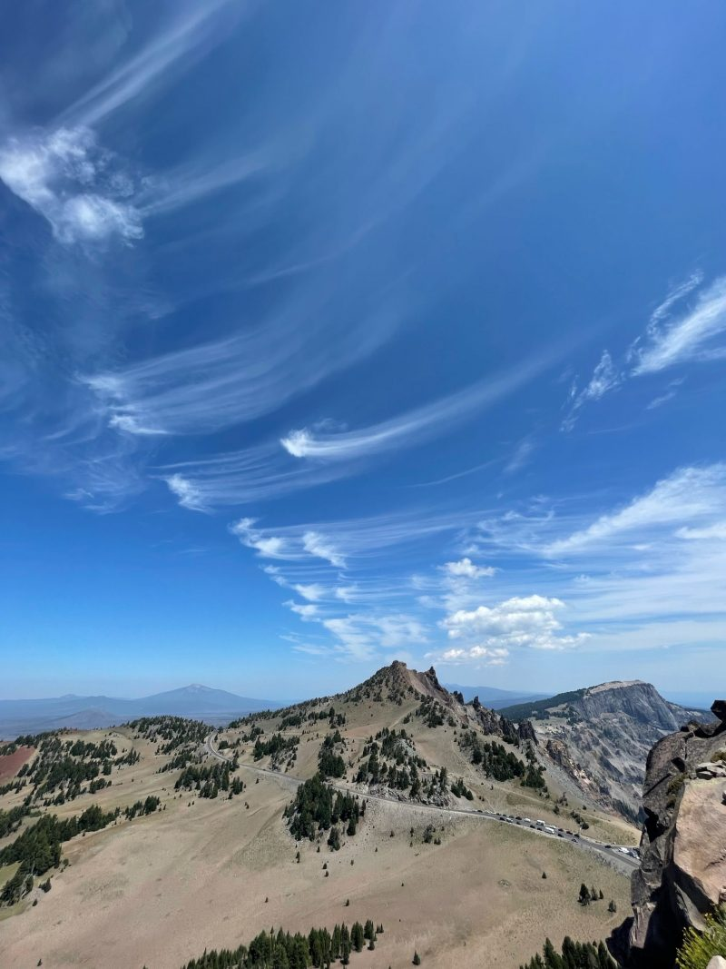 Mares' tails appear as streaks of wispy clouds in a blue sky, hook-shaped at one end, here over pointy mountains.