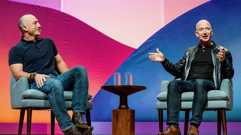 Two balding men in jeans and dark shirts, seated on a stage, discussing Jeff Bezos' Blue Origin flight.