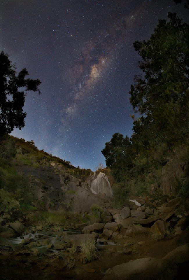 Arcing starry cloud over darkened waterfall.