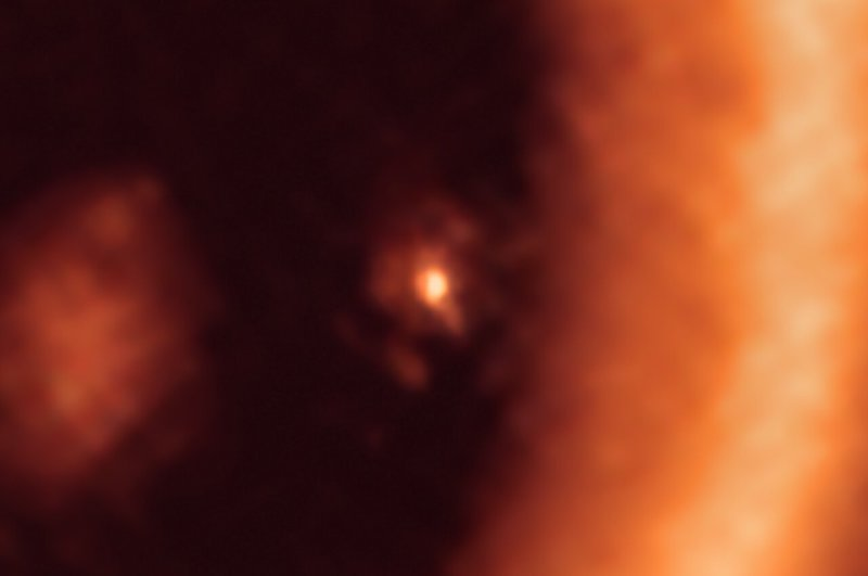 Bright dot with fainter smudge around it, and larger brighter regions on either side.
