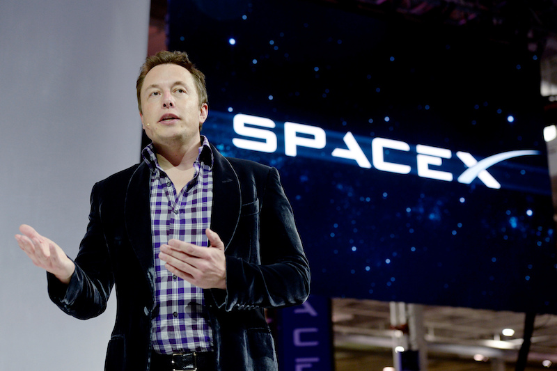 Elon Musk in plaid shirt and dark jacket addressing a group; large SpaceX logo in the background.